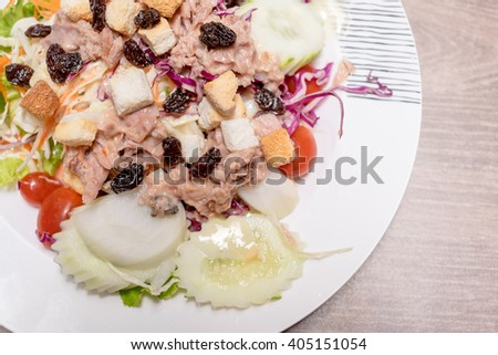 Tuna salad with different vegetables on wood table