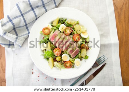 Tuna salad with fresh vegetables served on white napkin on wooden table - stock photo