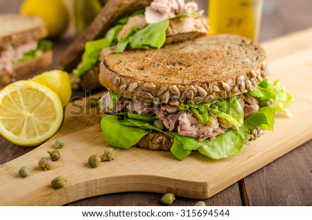 Tuna sandwich, capers, seed bread, lemon juice for freshness, little bit of dijon mustard and olive oil - stock photo