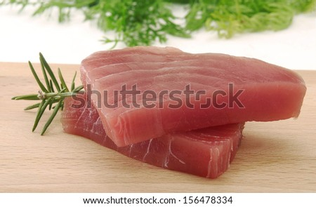 Tuna steaks and rosemary ingredient.Tuna fish slices. - stock photo
