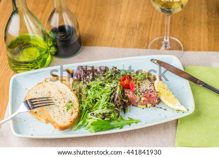 Tuna tartar - a healthy and delicious dinner . Snack on fresh fish close-up on a wooden table .  - stock photo