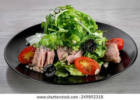 Tune ceaser salad on black plate on wooden table - stock photo
