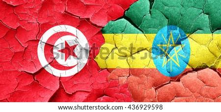 Tunesia flag with Ethiopia flag on a grunge cracked wall - stock photo