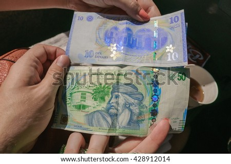 Tunesian dinar, national currency in the hands, - stock photo