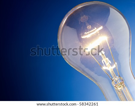 tungsten lightbulb on blue background. Horizontal shape, copy space - stock photo