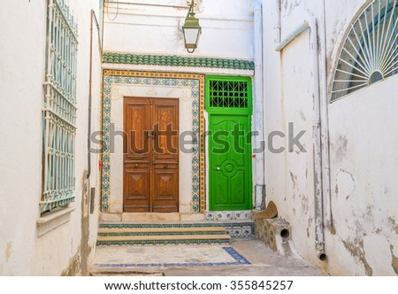 TUNIS, TUNISIA - SEPTEMBER 3, 2015: Two wooden doors in the narrow yard are always together, on September 3 in Tunis.