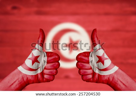 Tunisia flag painted on female hands thumbs up with blurry wooden background