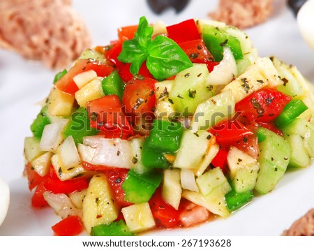 Tunisian salad with tomatos, cucumbers and tuna garnished with fresh basil leaves - stock photo