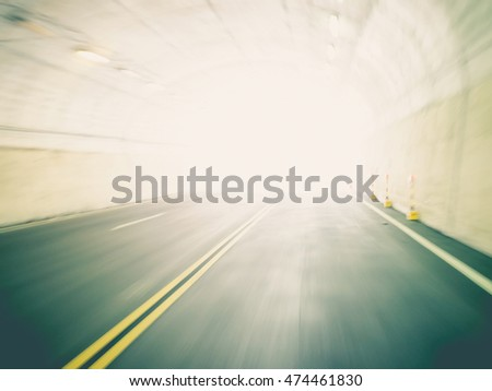 Tunnel exit background. Bright glowing light with motion blur. Toned image.
