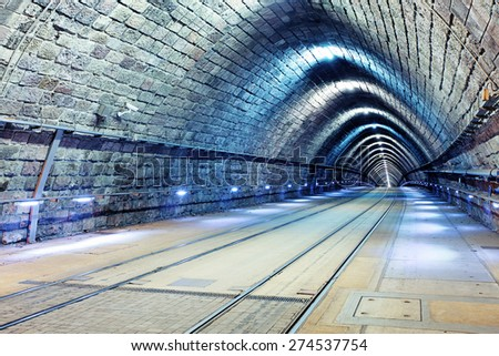 Tunnel with railroad and tram - stock photo