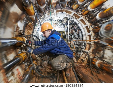 Tunneller sinker worker connecting equipment in tunnel of sewe? collector at undergroung working - stock photo