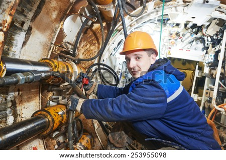 Tunneller sinker worker connecting equipment in tunnel of sewer collector at undergroung working - stock photo