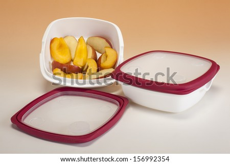 Tupperware containing pieces of fresh fruit - stock photo
