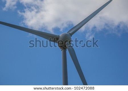 Turbine with blue sky and a cloud - stock photo