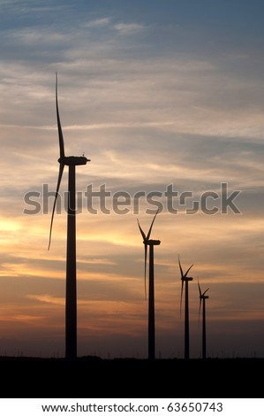 Turbines at a large midwestern wind farm are silhouetted against a sunset