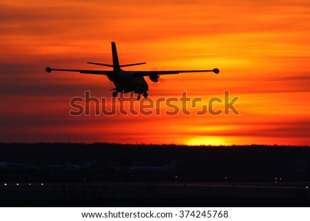Turboprop airplane landing on a sunset.