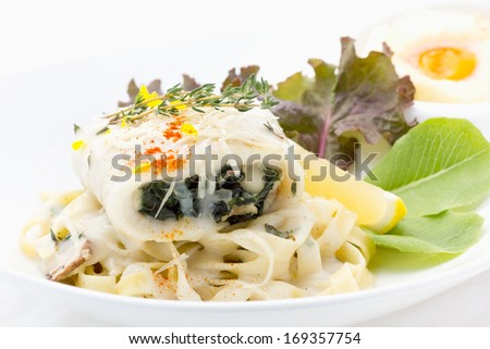 Turbot fiffet stuffed with spinach royale served with fettuccine veloute sauce and a side of baked egg in bread bowl - stock photo