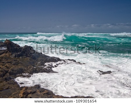 Turbulent ocean waves with white foam beat coastal stones - stock photo
