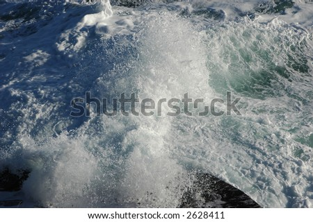 Turbulent stormy waters at the cliff base - stock photo