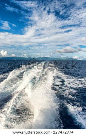 Turbulent wake leaving a trail of white water through the ocean behind a speeding motorboat - stock photo