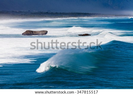 Turbulent water of breaking ocean waves and spray on incoming ocean surf on West Coast of New Zealand South Island