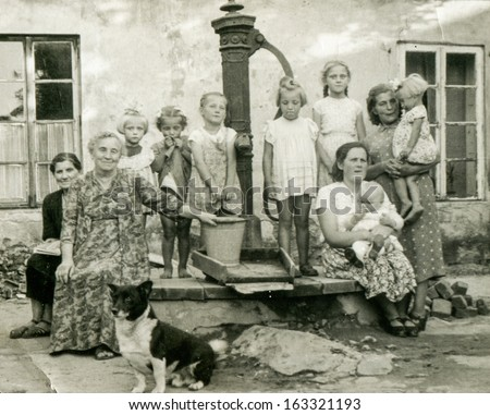 TUREK, POLAND, CIRCA FIFTIES -  unidentified women with children and dog (multigenerational family and neighbors) posing outside, in front of water pump,  - in Turek, Poland, circa fifties