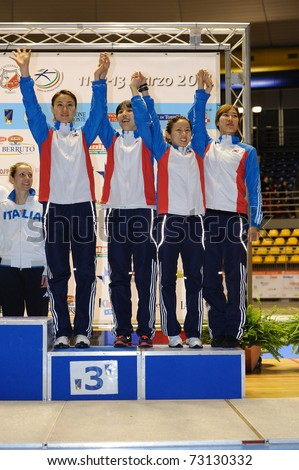 TURIN, ITALY - MARCH 13: Korea team (JEON, NAM, OH, SEO) stands at first place podium of team tournament of the 2011 Women world fencing cup on March 13, 2011 in Turin, Italy - stock photo