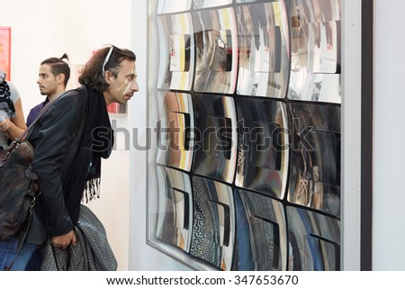 TURIN, ITALY - NOVEMBER 6: Artissima, contemporary art fair opening with people, galleries and art collectors on November 6, 2015 in Turin, Italy. Man looking at mirror artwork. - stock photo