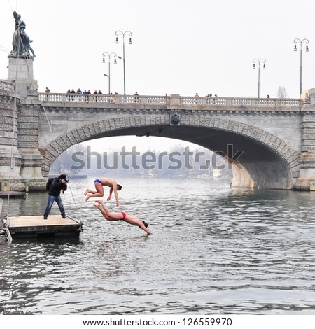 TURIN - JANUARY 27: The challenge plunge of the people named polar bears into the cold winter waters of river Po, a traditional annual event that starts the new year, on January 27, 2013 Turin, Italy. - stock photo