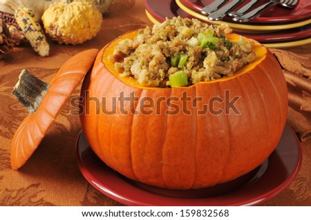 Turkey and celery stuffing in a pumpkin on a holiday dinner table - stock photo