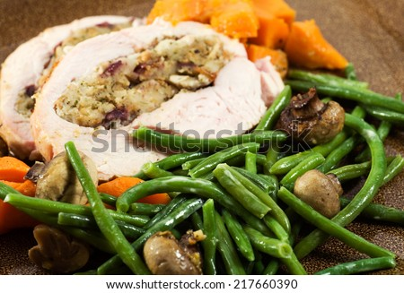 Turkey breast stuffed and roasted with cranberry, apple stuffing, carrots and sweet potato. Steamed fresh green beans and garlic roasted mushrooms.  - stock photo