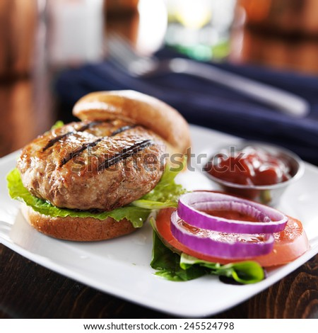 turkey burger on bun with lettuce and fixings - stock photo