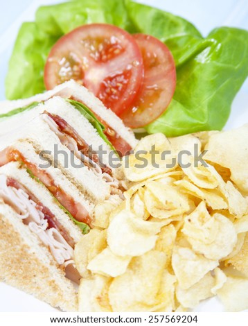 Turkey Club Sandwich with chips - stock photo
