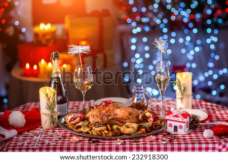 Turkey garnished with potato, apples and garnet on Christmas decorated table - stock photo