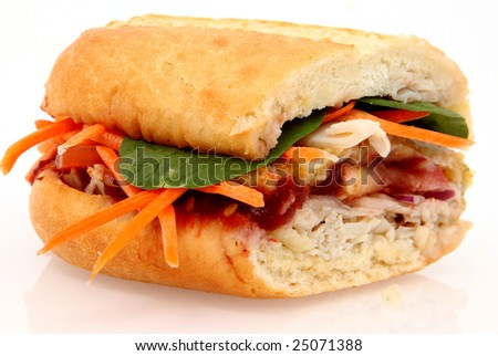 Turkey meat, dressing, cranberry sauce, carrots, spinach on a sub bun.