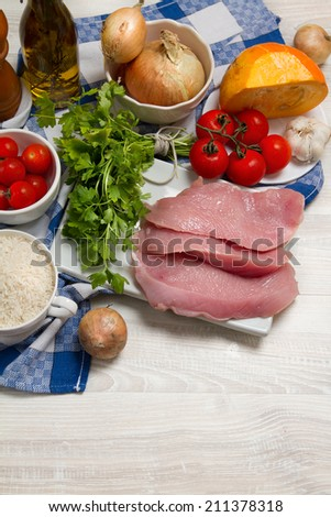 Turkey meat, parsley, tomatoes, onion, pumpkin, garlic and rice on the table