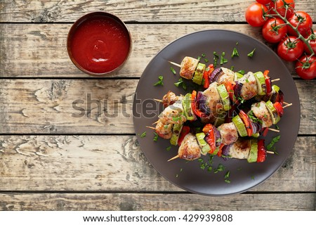 Turkey or chicken meat shish kebab skewers with ketchup sauce, and tomatoes on rustic wooden table background. Traditional barbecue grill shish food - stock photo