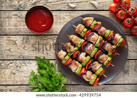 Turkey or chicken meat skewers shish kebab grilled food with onion, tomatoes, parsley and ketchup on rustic wooden table. Traditional barbecue shish - stock photo