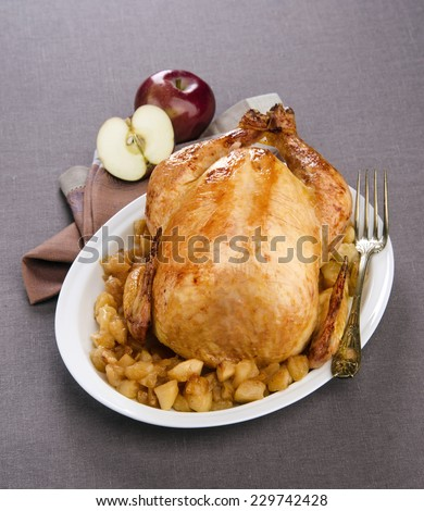 turkey stuffed with apples on a white plate decorated with apples on a dark tablecloth - stock photo