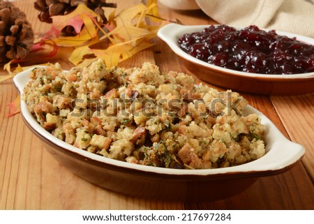 Turkey stuffing and cranberry sauce on a holiday table with autumn leaves and pine cones - stock photo