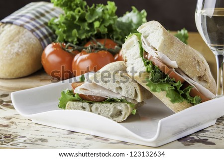 Turkey sub on rustic bread with tomato, bread, lettuce and cheese in the background - stock photo