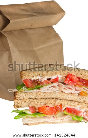 Turkey tomato and lettuce sandwich brown bag lunch - stock photo