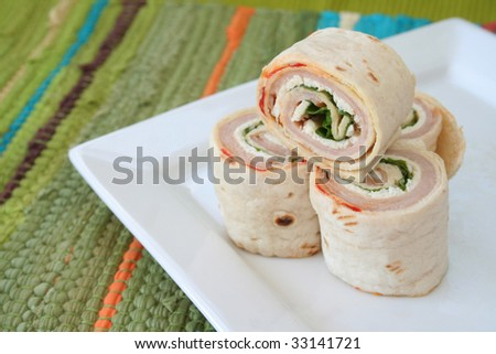 Turkey wraps stacked on a white plate with one laying over on it's side.  Used a selective focus with the top wrap being the main subject. - stock photo