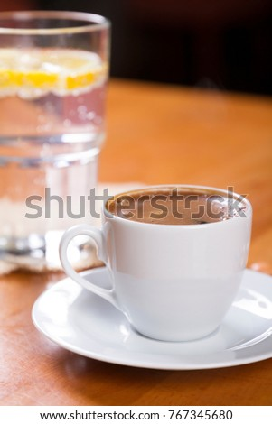 Turkish and Arabic Black Coffee in special design glass with white plate, drinking water, lemon slice, cookie, biscuits,bonbon, chocolate and nuts on wood table background. Copy Space.