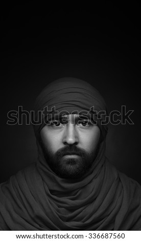 Turkish and Arabic theme: beautiful Muslim man with a beard in a red headscarf isolated on a black background in studio, black and white photography