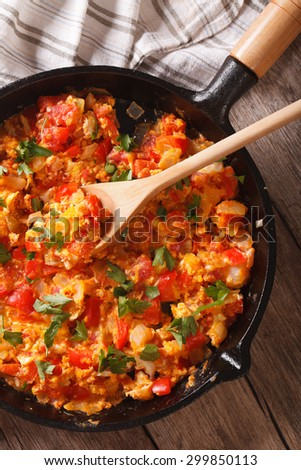 Turkish breakfast: Menemen in a pan close-up vertical view from above