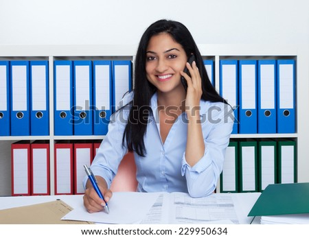 Turkish businesswoman with phone at office - stock photo