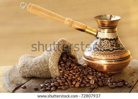 Turkish coffee in a copper Turks and grains are scattered on the wooden surface - stock photo