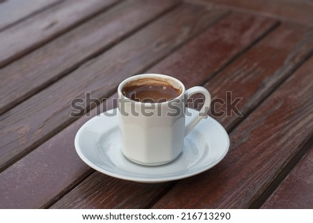 Turkish coffee in a white cup on the table - stock photo