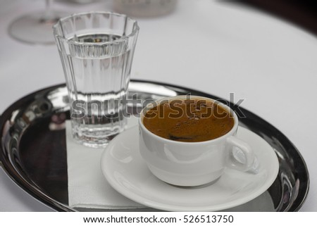 Turkish coffee in a white modern cup with a glass of water.